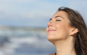 Closeup portrait of a relaxed woman breathing fresh air on the beach